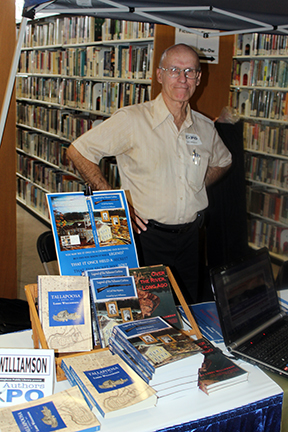Larry Williamson stands next to copies of his new novel, Legend of the Tallassee Carbine as well as his award-winning Tallaspoosa and Over the River, Long Ago at the Birmingham Library's Local Author Expo.