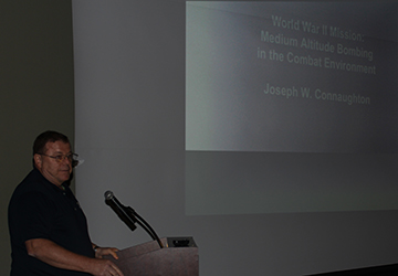 Jamie Dodson, a former U.S. Army intelligence and special ops officer, introduces Joe Connaughton to a crowd of over 200 people at the Huntsville Museum of Art during its Memories of World War II exhibition.