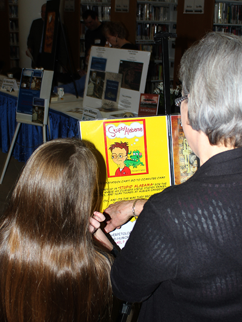 Fans look over the poster for Michael P. Wines, Stupid Alabama, at the Birmingham Library's Author Expo 2014